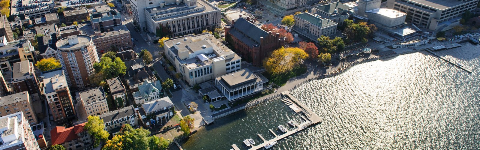 The Lake Mendota shoreline is pictured in an aerial view of the University of Wisconsin-Madison campus during autumn on Oct. 12, 2013. Clockwise from bottom center, major campus facilities include the Goodspeed Family Pier, Below Alumni Center, Pyle Center, Memorial Library, Mosse Humanities Building, construction of the East Campus Mall, Wisconsin State Historical Society, Science Hall, Helen C. White Hall, Memorial Union Terrace and Red Gym (Armory and Gymnasium). The photograph was made from a helicopter looking south. (Photo by Jeff Miller/UW-Madison)